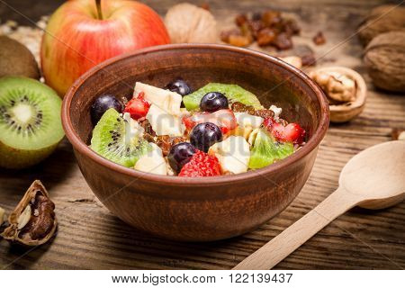 Morning breakfast with oatmeal and fruits in bowl on old wooden table