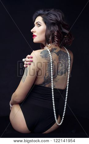 A beautiful young  caucasian adult woman sitting on a bad, with her back to the camera, , wearing a sexy lingerie, red lipstick and a string of pearls.
