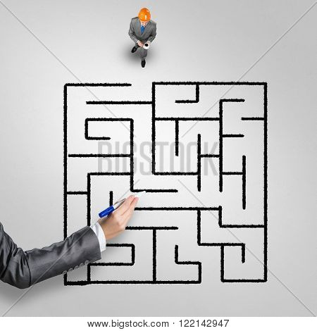 Top view of businessman in helmet with cup of coffee and drawn maze on floor