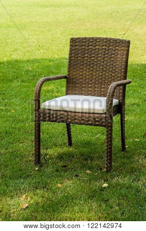 Rattan chair with cushion in the garden