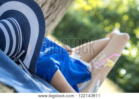 Woman wearing a straw hat relaxing by lying in summer nature with her legs crossed holding a cold drink. Focus to her hat.