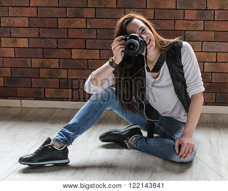 smiling girl taking photo with dslr camera in funny positions