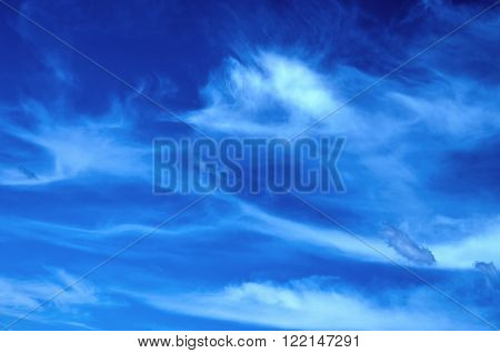 White cirrus clouds against the blue sky