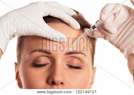 Beautiful woman with closed eyes surgeon in medical gloves is making an injection in face isolated on a white background close-up