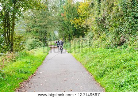 ESSEN, GERMANY - SEPTEMBER 30, 2014: Group of older men cycling on the promenade of the river Ruhr near Essen Werden towards Kettwig.
