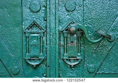 old green metal door and hand crank