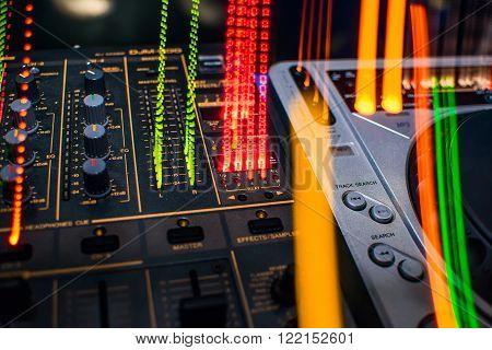 DJ mixer in night club colored closeup
