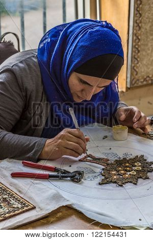 Madaba, Jordan - October 27, 2015: Woman is making artistic mosaics. Madaba is best known for its Byzantine mosaic, especially a large Byzantine-era mosaic map of The Holy Land.