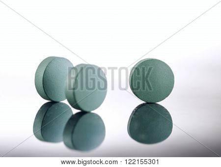 Green medicine pills on white background. Pharmaceutical medicament. Antibiotic painkiller or narcotic closeup.
