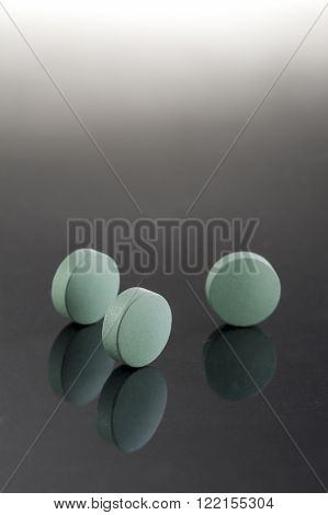 Green medicine pills. Pharmaceutical medicament. Antibiotic painkiller or narcotic closeup.