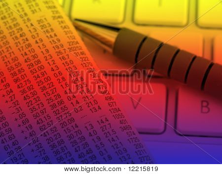 Financial newspaper resting on laptop keyboard with color lighting effect