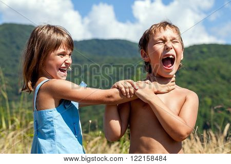 Angry boy and a girl scream and fight with each other outdoors