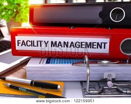 Red Office Folder with Inscription Facility Management on Office Desktop with Office Supplies and Modern Laptop. Facility Management Business Concept on Blurred Background. 3D Render.