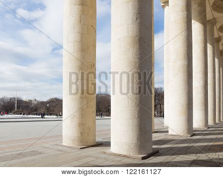 Moscow - March 13 2016: Central entrance to the Park of Culture and Rest named after Gorky a colonnade and people walking in the park March 13 2016 Moscow Russia