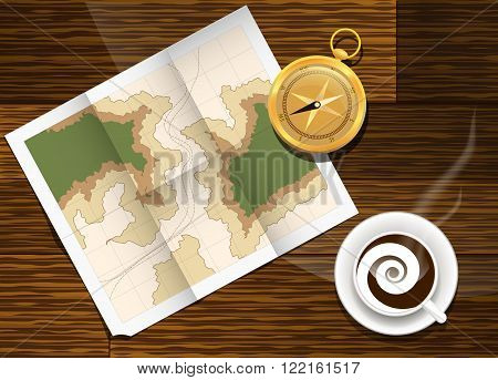 Paper map lying on the table next to the compass with cup of cofee.