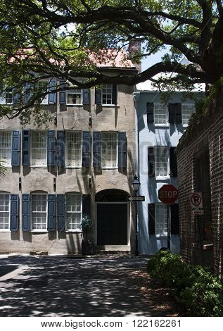 View of two historical buildings and their many traditional windows and shutters in downtown Charleston, South Carolina along a shady southern historical cobblestone street