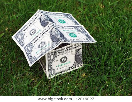 Conceptual image showing house shape made from US dollars on grass