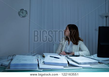 Young Businesswoman Checking Time On Wall Clock In Office
