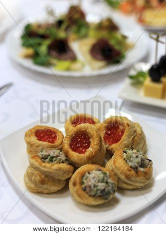 Close up photo with selective focus of red caviar profitroles served on white table next to salad profitroles in buffet