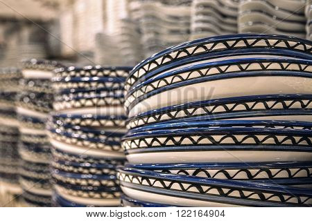 Stacks of plates with the national pattern of the Jordan. Close-up with a small depth of field. Jordanian souvenir shop.