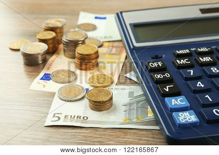 Money concept. Black calculator with banknotes and coins on wooden table, close up