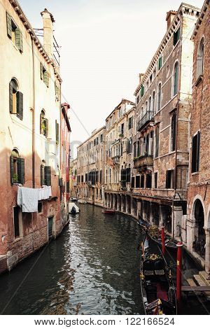 Venice, Italy - September 22, 2015: venetian canal narrow street between old aged residential buildings with black gondola at mooring in sea lagoon on townscape background, vertical picture