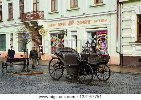 CHERNIVTSI ,UKRAINE - DECEMBER 1 2015: Olga Kobylyanska avenue (only one pedestrian street in town)with iron carriage - gift from blacksmith guild on December 1 in Chernivtsi, Ukraine.It is historical center of Chernivtsi and popular walking route