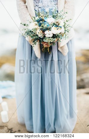 the bride's bouquet in hands of the girl who stands on the rocks in a gray dress