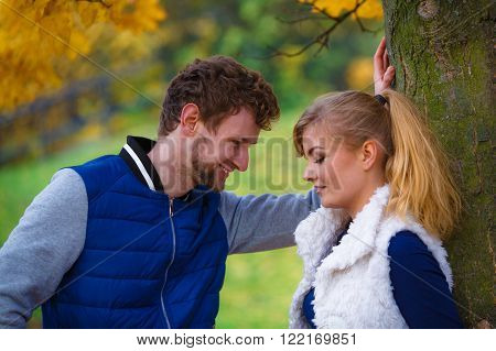 Season, happiness and people concept. Young romantic couple relaxing in autumnal park enjoy romantic date on sunny day