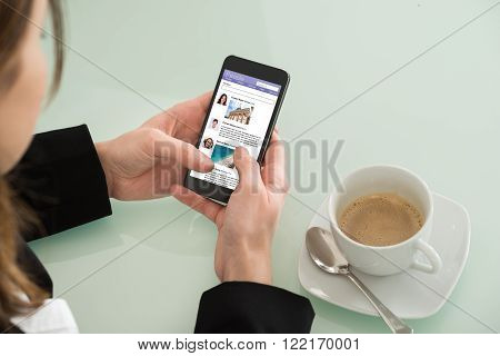 Close-up Of Young Businesswoman Surfing Social Networking Site On Mobilephone