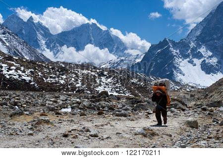 SAGARMATHA NATIONAL PARK NEPAL - MARCH 16: Porters carry heavy load in the Himalaya on March 16 2014 in Sagarmatha National Park Nepal