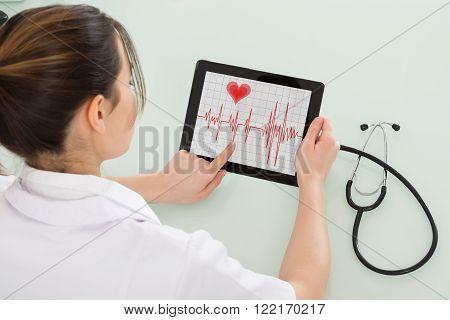 Female Cardiologist Analyzing Heartbeat On Digital Tablet