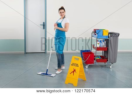 Female Janitor Mopping Corridor