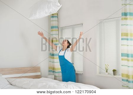Female Housekeeper Throwing Pillow