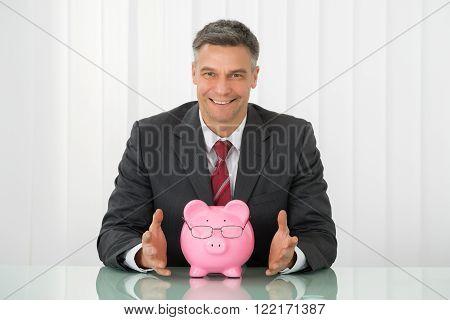 Happy Businessman With Piggybank Wearing Eyeglasses On Desk