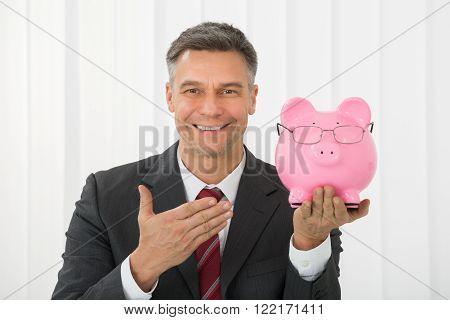 Mature Happy Businessman Holding Piggybank In Office
