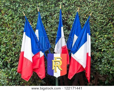 5 French flags fixed to a pole with the arms of Republic of France during the national celebrations on the 14th of July.