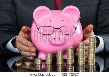Close-up Of Businessman Hand Sheltering Piggybank And Coins At Desk