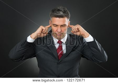 Portrait Of Mature Businessman With Eyes Closed And Fingers In His Ears