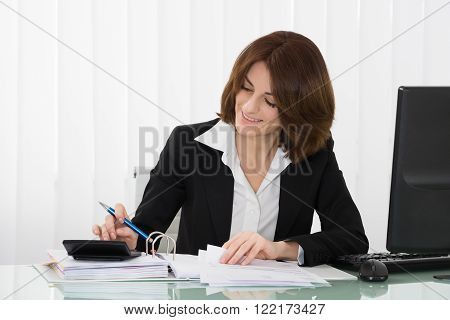 Happy Businesswoman Calculating Tax At Desk In Office