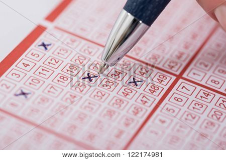 Woman Marking Number On Lottery Ticket With Pen