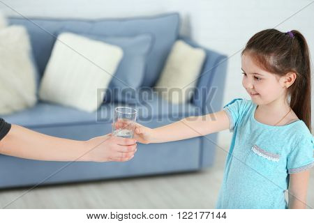 Little girl getting glass of water in living room
