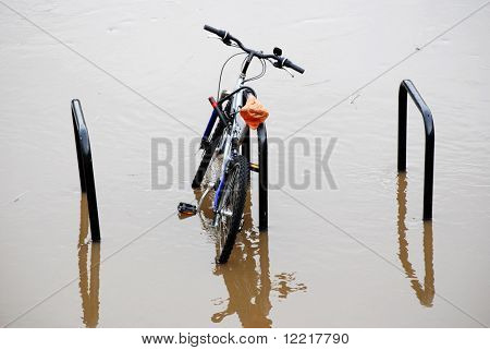 Abandoned bicycle caught in flood waters. York, North Yorkshire, UK.