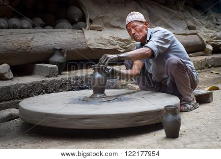BHAKTAPUR NEPAL - APR 5: Unidentified Nepalese potter working in the his pottery workshop Apr 5 2014 in Bhaktapur Nepal.