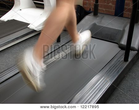 Man running on mechanical treadmill in gymnasium
