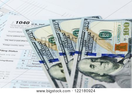 1040 Individual Income Tax Return Form with one hundred dollar bills, close up
