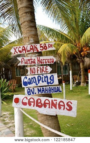 Colorful wood signs provide direction in a Costa Maya resort area.