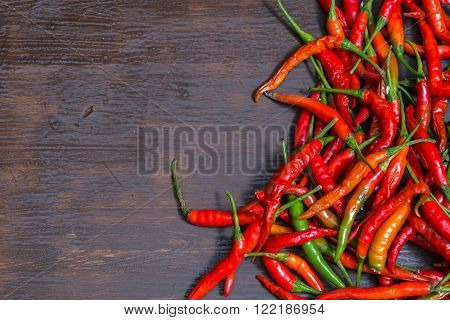 Chilli on wooden background, overhead view. low key tone.