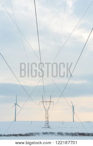 Windmill And Powerlines On The Field In Winter