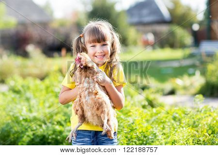 Child little girl with hen outdoor